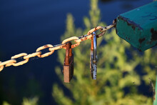 Two Padlocks Pinned To A Rusty Chain Hanging Above The Water