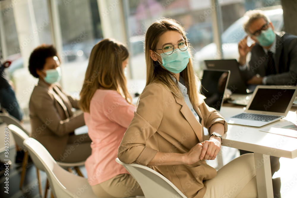 Fototapeta Young woman with group of business people have a meeting and working in office and wear mask as protection from corona virus