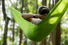 Woman Relaxing In Hammock In T...