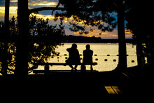 Silhouette Friends Sitting On Bench Against Lake During Sunset