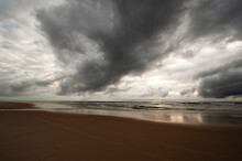 Dark Clouds Over The Sandy Beach