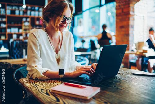 Obraz na plátně Positive female freelancer in eyewear typing on laptop computer creating publica