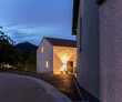 Leinwanddruck Bild - Single-family house, exterior seen in the evening. Single-family house in a small Swiss village