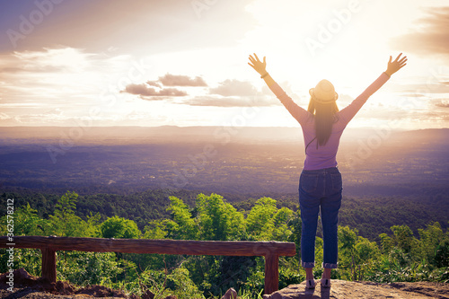 Woman happy stands with raised arms at sunset mountain and enjoys sunset Fototapete