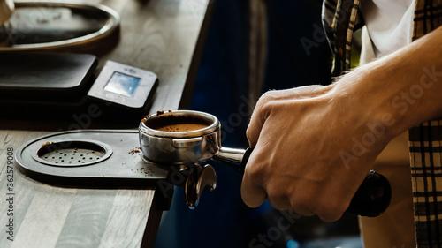 Stampa su Tela Barista presses ground coffee using tamper