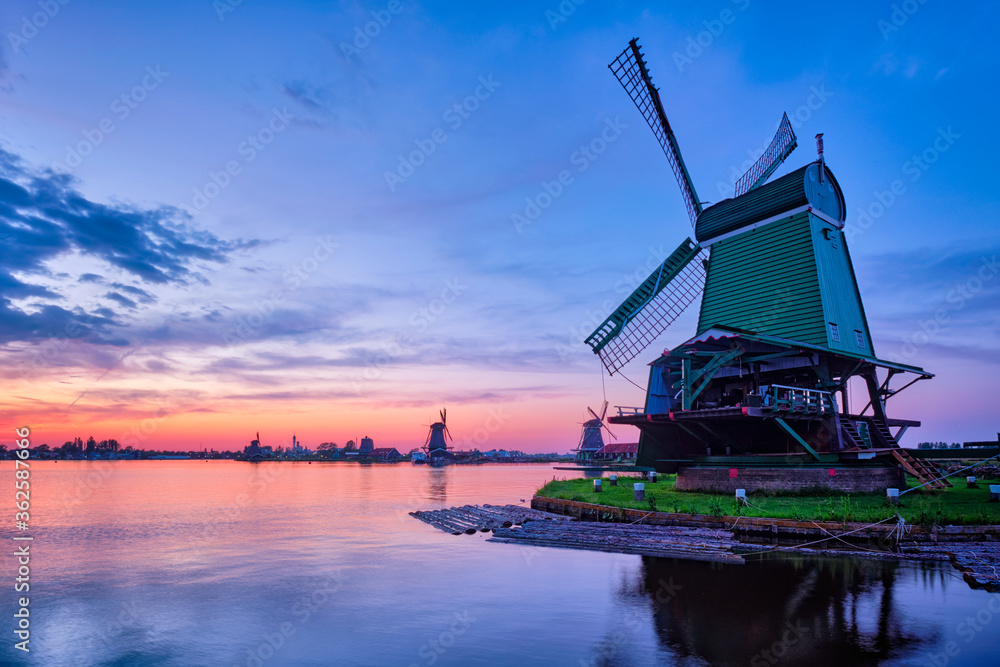 Fototapeta Netherlands rural scene - windmills at famous tourist site Zaanse Schans in Holland on sunset with dramatic sky. Zaandam, Netherlands