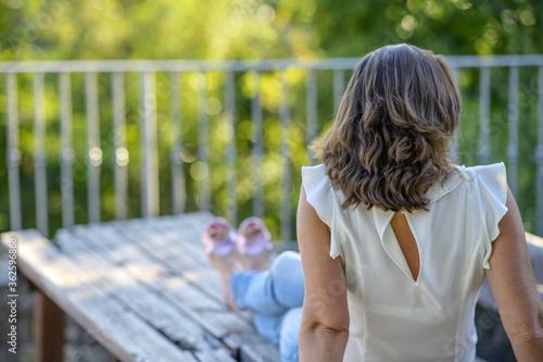Vászonkép Donna ritratto seduta su un muro stradale
