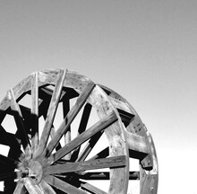 Low Angle View Of Wooden Water Paddle Wheel Against Clear Sky In Black And White