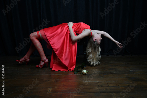 Fotomural beautiful girl in evening red dress posing with a white rose on a black backgrou