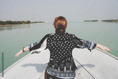 Canvas Print Rear View Of Woman With Arms Outstretched Standing On Rowboat In Sea Against Sky