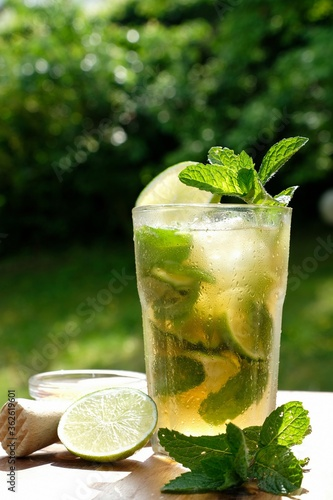 Fototapeta Non Alcoholic Mojito In Cocktail Glass On Wooden Table. Ice Cubes, Pepper Mint Leaves, And Ice Cubes obraz
