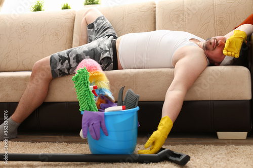 Male lying on the couch and sleeping after cleaning the house Canvas Print