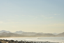 Surfer Rides His Surf Board On White Wave Pacific Coast Of Baja, Mexico With Hills And Mountain