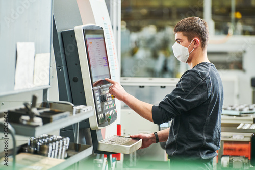 Fotomural Industrial worker operating cnc machine in protective mask at metal machining in