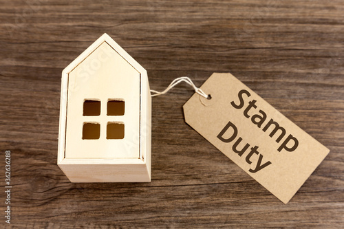 Wooden house with label attached which reads 'Stamp Duty' Fotobehang