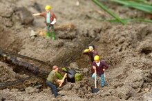 Close-up Of Worker Figurines Digging Dead Dragonfly On Field