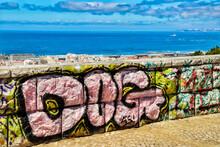 Graffiti On Wall By Sea Against Sky