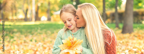 Obraz Happy young caucasian mother and little daughter holding autumn yellow leaves sitting and kissing at the park - fototapety do salonu