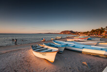 Rowboats Moored At Beach Against Sky During Sunset