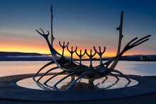Close-up Of Silhouette Sculpture Against Sea During Sunrise - Sun Voyager