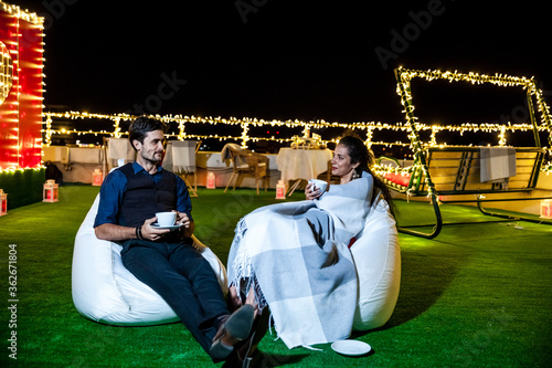 Платно Young Couple Having Coffee While Relaxing On Illuminated Terrace At Night
