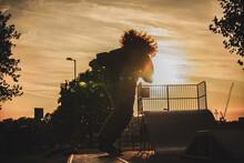 Silhouette Man Skateboarding In Park Against Sky During Sunset