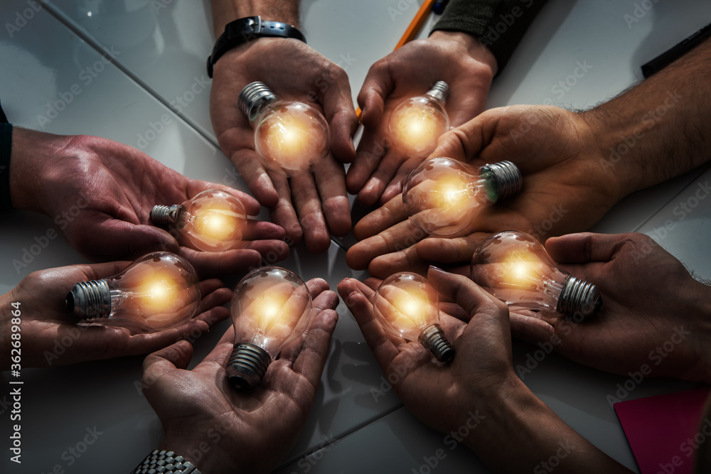 Fototapeta Teamwork and brainstorming concept with businessmen that share an idea with a lamp. Concept of startup