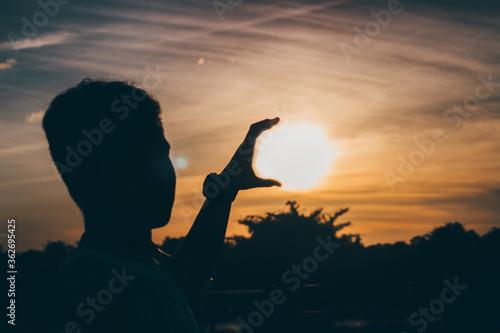 Fototapeta premium Optical Illusion Of Silhouette Man Holding Sun Against Sky During Sunset