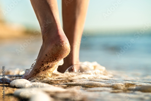 Fotografie, Obraz Close up of woman feet walking barefoot on sand beach in sea water