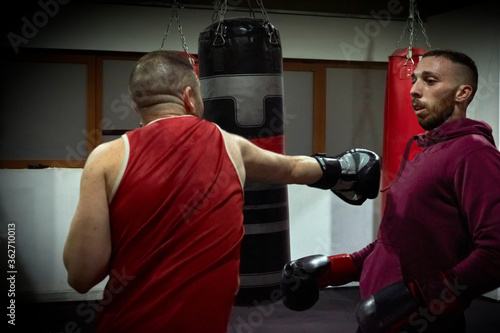 Determined male boxers practicing in health club
