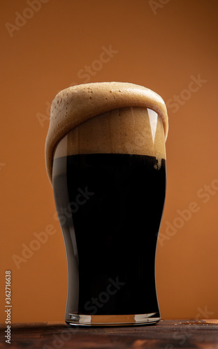 Fotografia Overflowing stout in a shapely pint glass