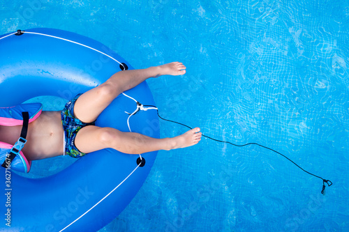 Boy bathing in a pool playing with a large round float. Fototapet