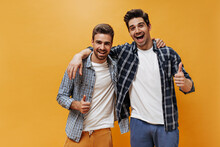 Excited Brunet Men In Checkered Shirts, Colorful Pants And White T-shirts Smile, Show Thumbs Up And Pose On Orange Background.