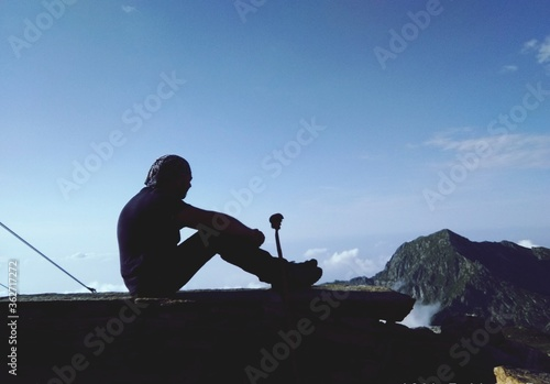 Fototapety, obrazy: Silhouette Man Sitting On Cliff Against Sky