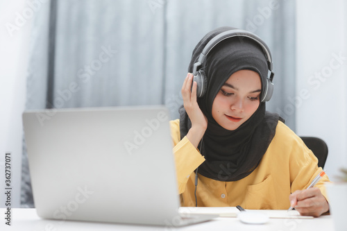 Beautiful muslim student girl using a laptop computer learning online at home Slika na platnu