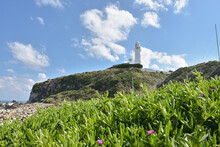 Lighthouse On Field By Mountai...