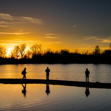 Silhouette People Fishing At Lake Against Sky During Sunset