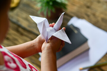 Little girl holding a white origami bird in her hands