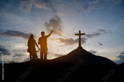 Cuadros en Lienzo Silhouette christian family standing with cross for worship God