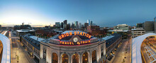 Union Station Panorama With Neon Travel By Train Sign And Clock And Denver City Skyline In The Background At Sunrise