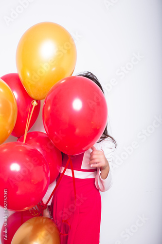 Fotografie, Obraz Girl With Red And Orange Balloons Standing Against White Background