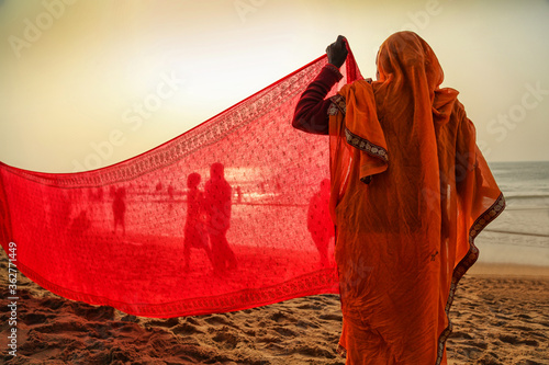 Fotografie, Tablou Indian women pilgrims drying their colorful sarees under sun after taking holy bath at puri beach