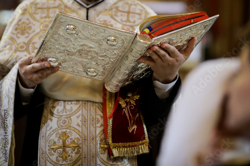 Tela Details of an Orthodox priest reading from the Holy Bible during an Orthodox Baptism