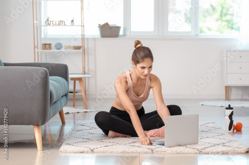 Fototapeta Sporty young woman with laptop training at home obraz