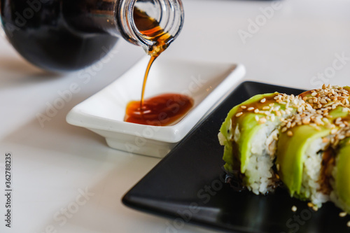 Bowl with tasty soy sauce. Sushi roll with eel and avocado. Traditional Japanese meal. #362788235