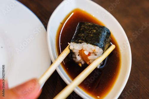 Bowl with tasty soy sauce and chopsticks on white background. Sushi roll with eel. Traditional Japanese food. #362788408