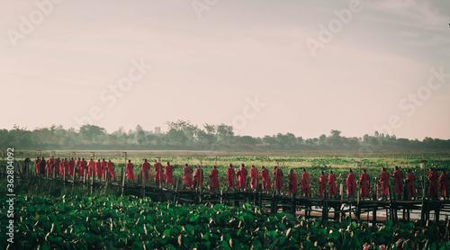 Valokuva Monks Standing On Field Against Sky During Sunset
