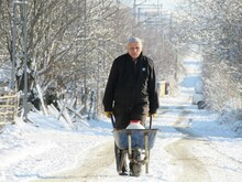 Man With Wheelbarrow On Road During Winter