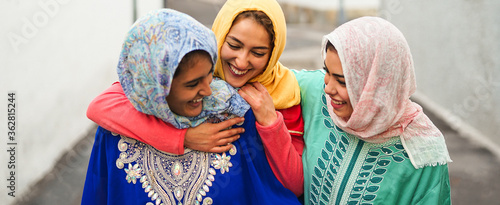 Obraz Happy Muslim women walking in the city center - Arabian young girls having fun spending time and laughing together outdoor - concept of lifestyle people culture and religion - fototapety do salonu