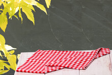 Closeup Of A Empty Red Checkered Tablecloth Or Napkin On A Rustic Bright Table Against Black Wall With Yellow Maple. Template For Food And Product Display Montage. Recipe Concept.